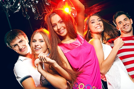 dancing disco: Company of cheerful teens enjoying themselves while dancing at disco Stock Photo