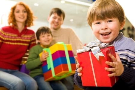 Portrait of handsome boy with giftbox on background of his parents and brother photo