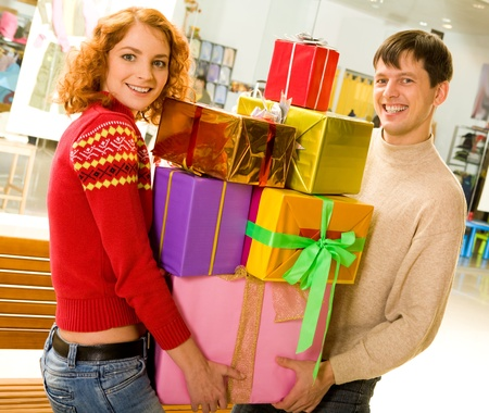 Portrait of shopaholics holding heap of presents and smiling at camera photo