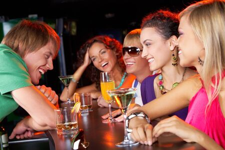 at the bar: Image of happy teenagers with cocktails chatting and having fun in the bar  Stock Photo