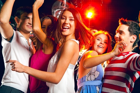 Pretty clubber dancing surrounded by her friends and looking at camera with smile photo