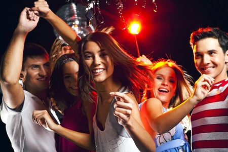 Image of energetic girl looking at camera while dancing on background of her friends Stock Photo