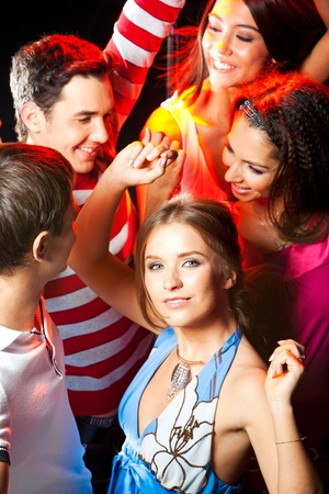 Gorgeous woman in smart dress dancing in crowd of clubbers photo