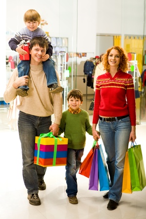 holiday spending: Portrait of family walking down shopping mall after buying Christmas presents Stock Photo