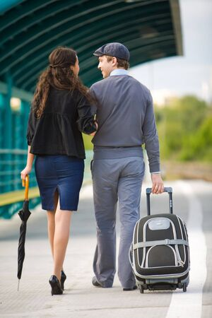 amorous: Rear view of amorous couple walking down station and chatting outdoors