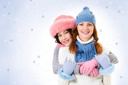 snowy background: Retrato de las ni�as felices mirando a la c�mara sobre fondo cubierto de nieve