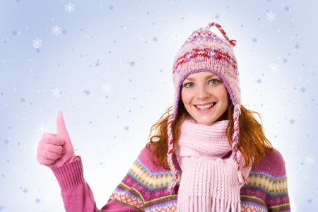 Image of cool girl showing thumb up over snowflake background photo