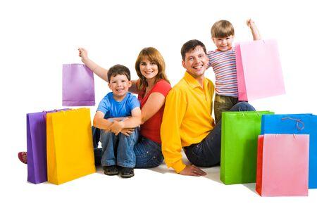 ni�os de compras: Imagen de padres felices y sus dos hijos, sentados en el estudio con bolsas de compra cerca por Foto de archivo