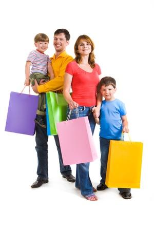ni�os de compras: Retrato de familia feliz de pie y la celebraci�n de bolsas mientras mira a la c�mara con sonrisas Foto de archivo