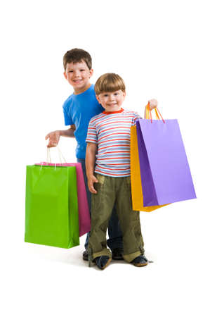 Portrait of brothers holding shopping bags and looking at camera happily photo