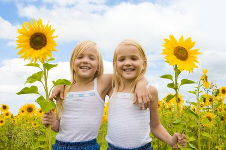 Portrait of cute girls looking at camera and smiling in sunflower field Stock Photo - 8508080