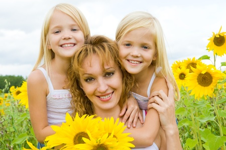 Portrait of cute twins embracing their mother with smiles in sunflower field photo