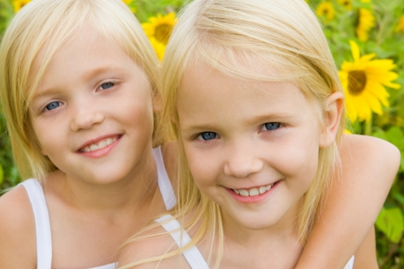 alike: Portrait of cute girl embracing her twin sister and both looking at camera with smiles