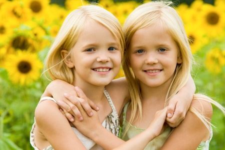 little girl smiling: Portrait of cute twins embracing each other on background of sunflower field Stock Photo