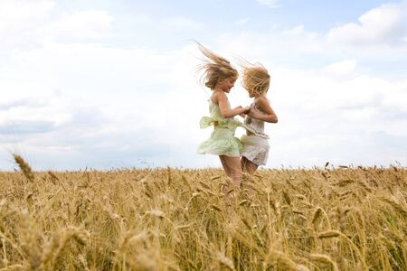 Portrait of energetic twin sisters whirling in wheat field and having fun Stock Photo - 8508079