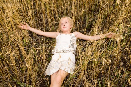 Image of youthful girl lying in wheat with peaceful expression photo