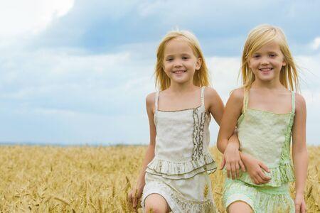 gemelas: Retrato de gemelos lindos caminando por el campo de trigo y sonriente