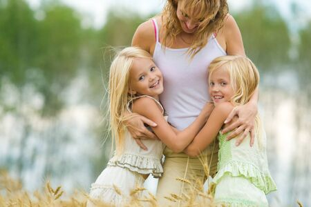 Twin sisters embracing their mother with smiles in wheat field photo