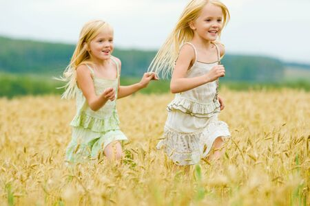 Portrait of happy girl running down wheat field with her twin sister behind Stock Photo - 8508054