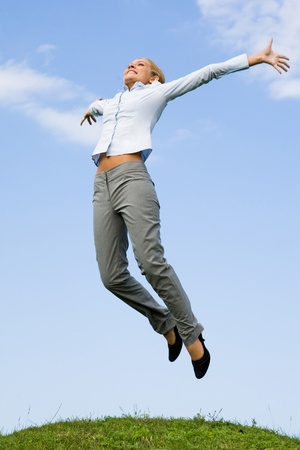 people attitude: Portrait of happy female jumping over green grass against blue sky Stock Photo