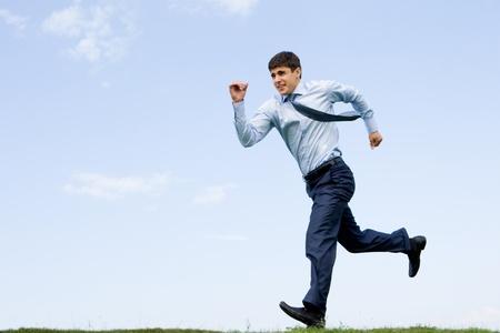 hombres corriendo: Empresario guapo corriendo por la hierba con cielo azul en segundo plano Foto de archivo