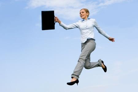 ブリーフケースの青い空を背景開いて空気中のジャンプと精力的な女性の肖像画 写真素材