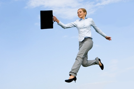 dynamics: Portrait of energetic female with briefcase jumping in open air against blue sky