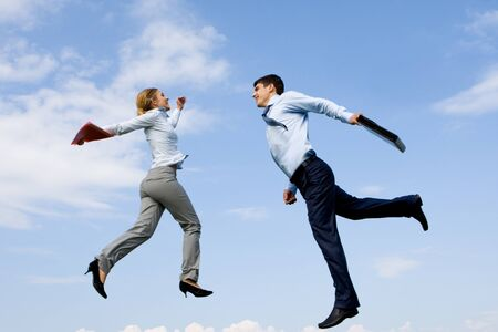 Portrait of happy partners jumping against blue sky photo