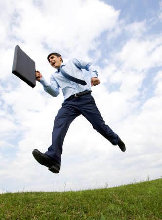 Handsome businessman with briefcase in hand leaping over green grass with cloudy sky at background Stock Photo - 8508226
