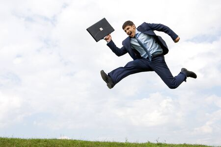 Handsome businessman in suit leaping over green grass with cloudy sky at background