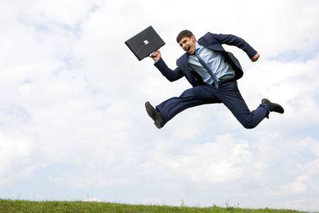 Knappe zaken man in pak springen over groen gras met bewolkte hemel op achtergrond