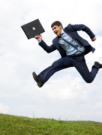 Well-dressed leader leaping over green grass with cloudy sky at background photo