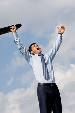 Portrait of screaming businessman with cloudy sky at background photo