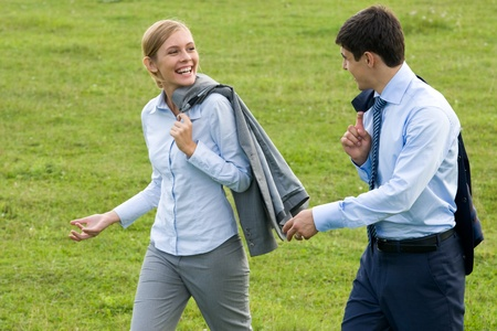 communicate: Rear view of associates walking down green grass and interacting Stock Photo