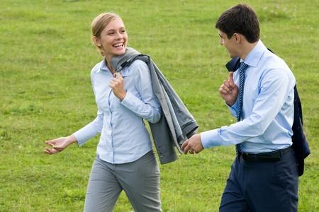 personas comunicandose: Vista posterior de asociados caminando por el pasto verde e interactuar