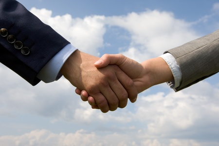 Photo of handshake of business partners on background of cloudy sky  photo