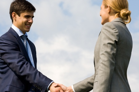 Photo of business partners handshaking on background of cloudy sky  photo