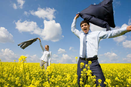 Portrait of happy business partners happily screaming in yellow meadow Stock Photo - 8508148