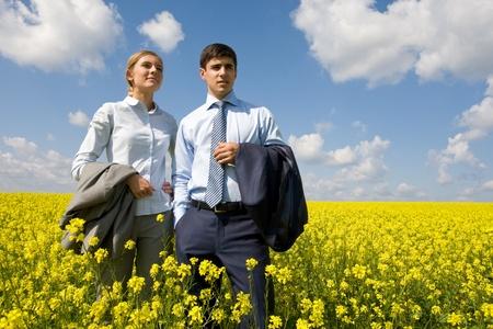 flower fields: Portrait of confident business partners looking forward against blue sky