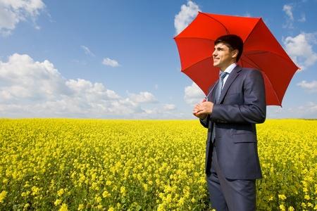 hombre rojo: Imagen de joven empresario con paraguas rojo en el campo de la flor Foto de archivo