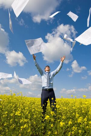winning mood: Image of happy winner throwing papers in yellow meadow Stock Photo