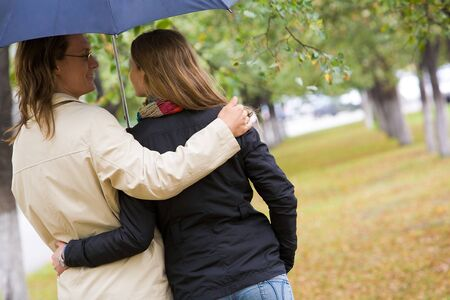 lovers park: Rear view of affectionate couple walking under umbrella Stock Photo