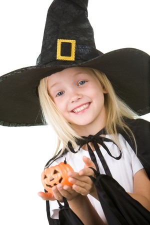 Portrait of girl in witch costume and small pumpkin in hands looking at camera Stock Photo