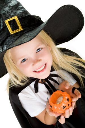 antichrist: Portrait of girl in witch costume and small pumpkin candle in hands