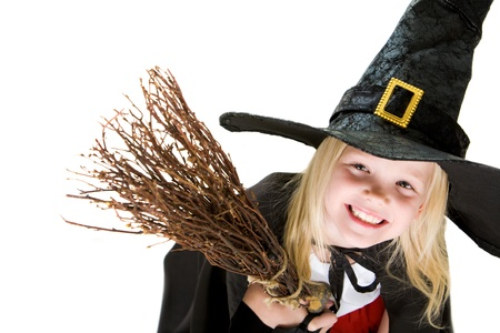 antichrist: Portrait of girl in halloween costume and broom smilling at camera Stock Photo