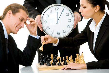 chess player: Image of businessman and businesswoman playing chess with businessman holding clock on background