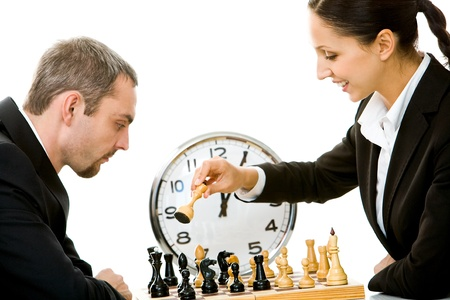 Image of businessman and businesswoman playing in chess with clock on background photo
