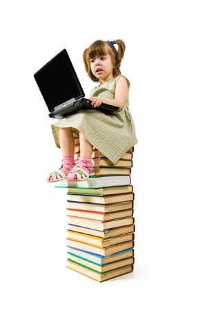 Image of typing preschool girl while sitting on top of book stack photo