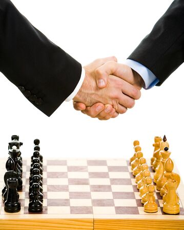 chess board: Image of chess-board with business handshake over it