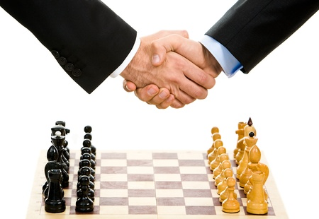 Image of chess-board with business handshake over it